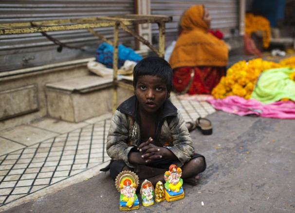 A child sells idols of gods at the corner of a street (Photo- Sushanta Das / AP)