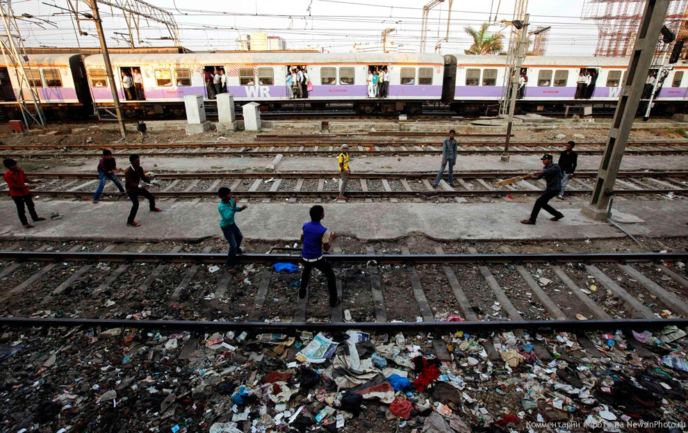 Boys make electric poles as wickets while playing cricket on railway tracks (Photo- Newsinphoto)