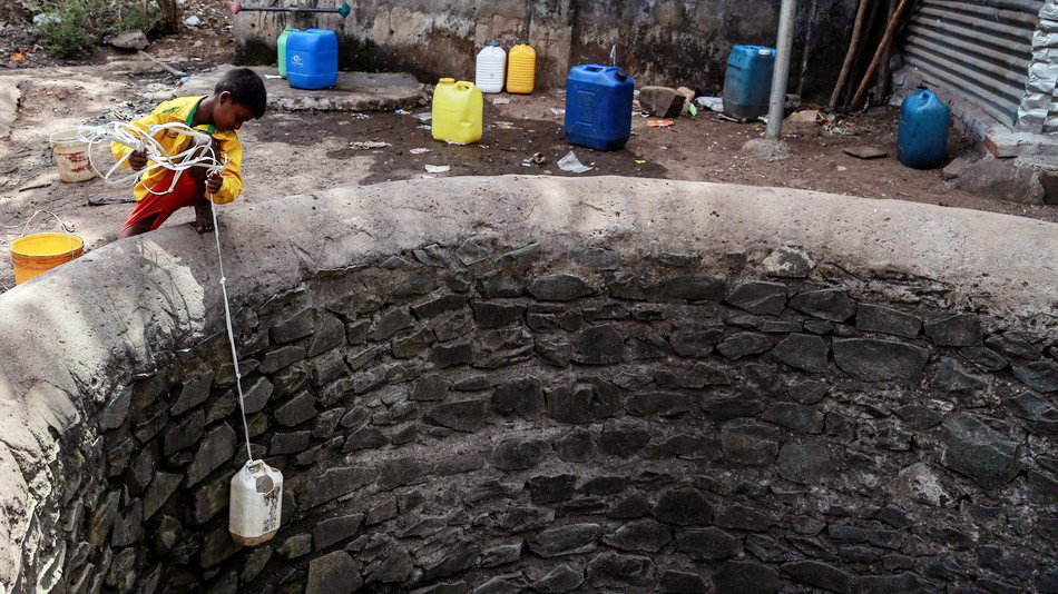 In a drought-affected village in Dindhori, Madhya Pradesh, children can be seen climbing down the walls of an almost dried-up well to fetch the remaining water. (Photo: Divyakant Solanki / EPA/Corbis Images)