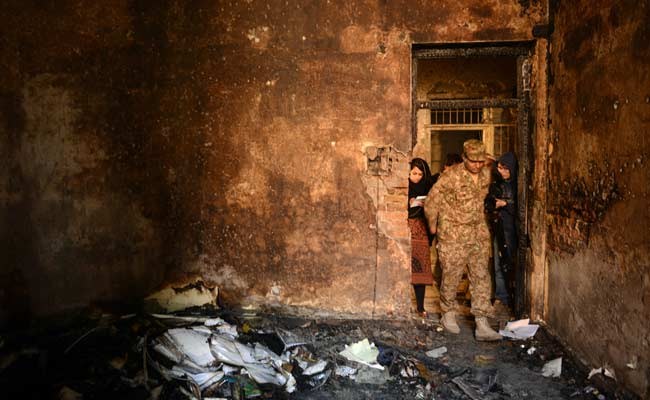 A pakistani soldier shows members of the media a burnt-out classroom, the day after the Taliban attack on a military school (Photo- A Majeed/AFP)
