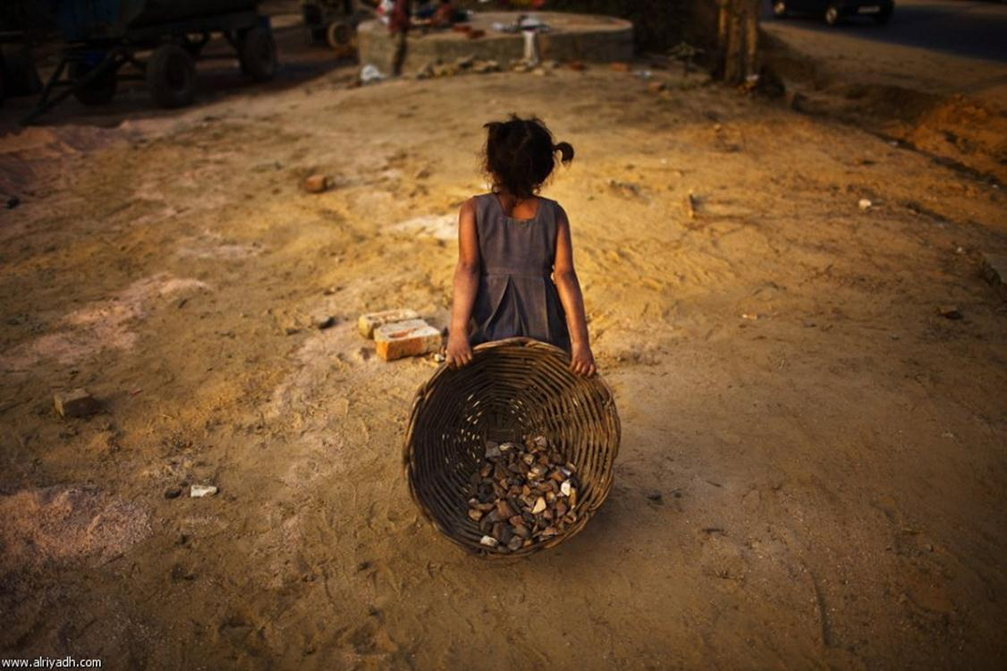 A girl drags a basket of gravel while working at a construction site in New Delhi (Photo- Getty images)