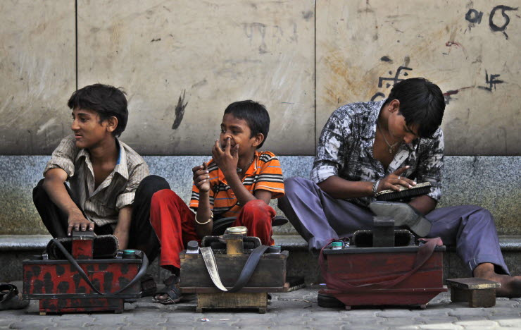 3 boys wait to polish shoes of commuters at a railway station (Photo- NY times)