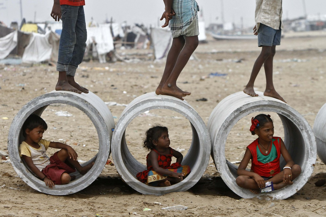 Children play their games amongst water pipes, oblivious to the dangers (Photo- Babu/Reuters)