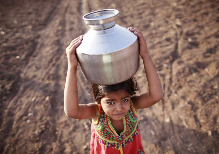 A little girl carries a metal pitcher filled with water through a field in drought-hit Latur n iMaharashtra (Photo: Danish Siddiqui/ Reuters)