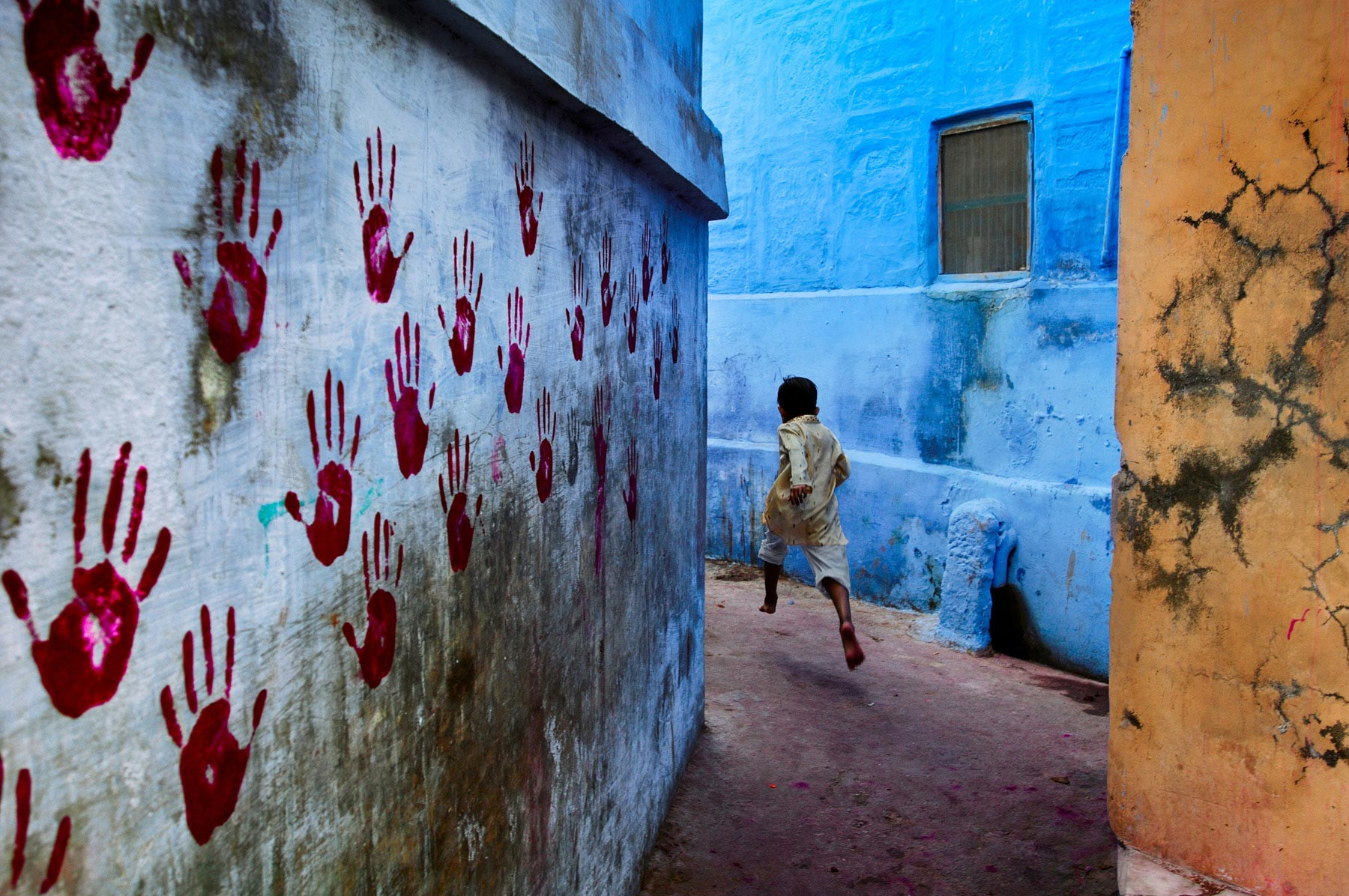 A child runs through the narrow gullies of Jodhpur, Rajasthan (Photo- Steve McCurry)