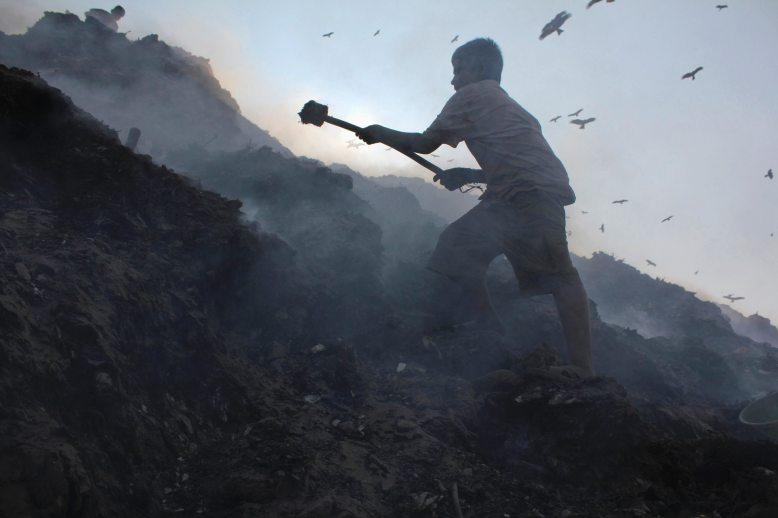A child waste collector uses a wooden stick to collect pieces of loose metal at a landfill in North India (Photo- Reuters)