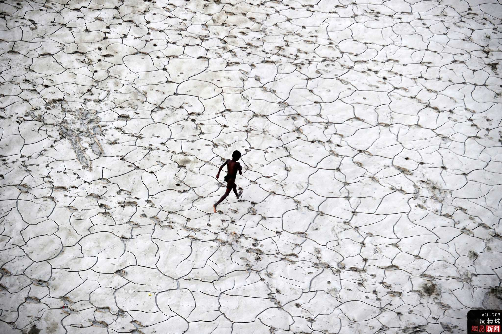 A child plays in a dry river-bed after the floods have receded in North India (Photo- Sanjay Kanojia/ AFP)