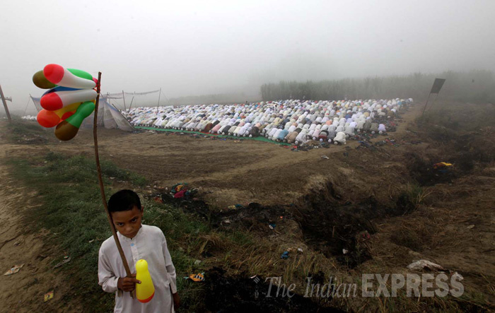 A refugee boy selling balloons as muslim refugees from Muzaffarnagar offer prayers during the Eid celebrations in open at a foggy and cold morning, near the relief camps at Malakpur village in Shamli district, Uttar pradesh (Photo: Ravi Kanojia)